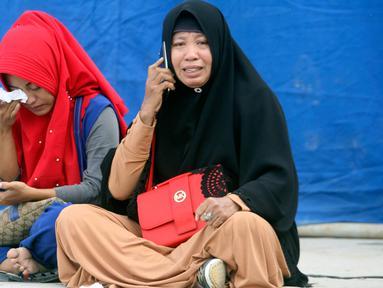 Kerabat menangis di pelabuhan Tigaras mengetahui keluarganya menjadi korban KM Sinar Bangun yang tenggelam di Danau Toba, Sumatera Utara, Rabu (20/6). KM Sinar Bangun yang mengangkut 128 penumpang tenggelam pada Senin (18/6) sore. (AP/Binsar Bakkara)