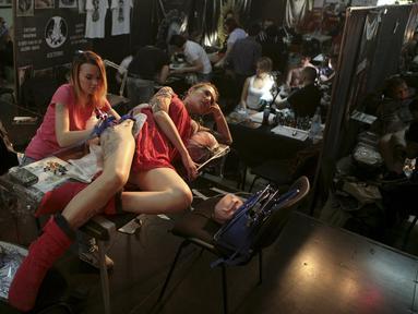 Seorang seniman membuat tato di punggung pelanggannya saat acara Festival Tato Internasional di Sochi, Rusia, (23/4). Sejumlah wanita tampak antusias untuk mentato tubuhnya di festival tato terbesar di negara tersebut. (REUTERS/Kazbek Basayev)