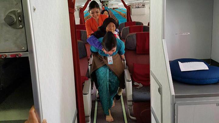 Foto pramugari Garuda Indonesia menggendong seorang nenek keluar pesawat menjadi viral. (Ist)