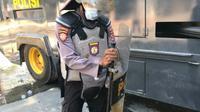 Seorang anggota polisi yang terkena lemparan kantong berisi tinja, demosntrasi yang digelar Senin (28/10/2019).(Liputan6.com/Ahmad Akbar Fua)