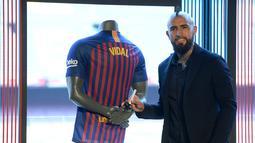 Pemain baru Barcelona, Arturo Vidal berpose usai menandatangani jersey dalam presentasi resminya di Stadion Camp Nou, Barcelona, Spanyol, Senin (6/8). (Josep LAGO/AFP)
