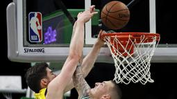 Pebasket Boston Celtics, Daniel Theis, menghadang dunk dari pebasket Indana Pacers, T.J Leaf,  pada laga NBA di TD Garden, Boston, Kamis (10/1). Celtics berhasil menang 135-108 atas Pacers. (AP/Charles Krupa)