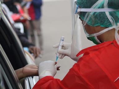 Petugas medis memberi pelayanan tes cepat diagnosa COVID-19 secara drive thru di titik pengecekan Terminal Jatijajar, Depok, Jawa Barat, Kamis (28/5/2020). Tes cepat ini hasilnya akan langsung dikonfirmasi melalui aplikasi dan dilaksanakan hingga Jumat (29/5).  (Liputan6.com/Helmi Fithriansyah)