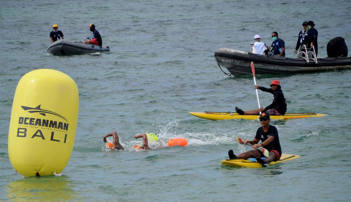 Para peserta bertanding sambil ditonton oleh kru pendukung dalam kompetisi renang Oceanman Bali 2021 di sebuah pantai di Sanur, Denpasar, Bali, Sabtu (18/9/2021). Oceanman Bali 2021 akhirnya sukses digelar setelah beberapa kali ditunda. (SONY TUMBELAKA/AFP)