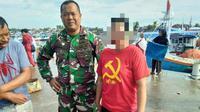 Emak-emak berbaju palu arit diamankan anggota TNI di tempat pelelangan ikan. (Liputan6.com/Fauzan)