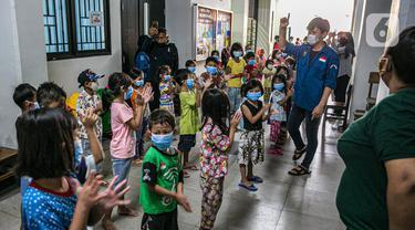 Relawan Forum Anak Jakarta Timur mengajak anak-anak korban banjir bermain di tempat pengungsian di Gedung SD Kampung Melayu 01/02, Kebon Pala, Jakarta, Selasa (9/2/2021). Trauma healing ini sengaja dilakukan untuk penanganan psikososial bagi anak-anak korban bencana. (Liputan6.com/Faizal Fanani)