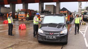 Petugas kepolisian memeriksa kendaraan di gerbang tol Cikupa, Kabupaten Tangerang, Banten, Kamis (6/5/2021). Pemeriksaan tersebut sebagai upaya untuk menyekat masyarakat yang nekat mudik seiring telah diberlakukan larangan mudik Lebaran mulai dari 6 hingga 17 Mei 2021.  (Liputan6.com/Angga Yuniar)