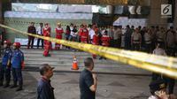 Sejumlah petugas bersiaga dekat garis polisi yang terpasang setelah ambruknya Selasar Tower II Gedung Bursa Efek Indonesia (BEI), Jakarta, Senin (15/1). Pelataran gedung BEI masih dipenuhi petugas yang melakukan proses evakuasi. (Liputan6.com/Johan Tallo)