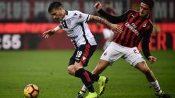 Bek AC Milan, Davide Calabria mencoba menghentikan pergerakan pemain Cagliari pada laga lanjutan Serie A yang berlangsung di stadion San Siro, Milan, Senin (11/2). AC Milan menang 3-0 atas Cagliari. (AFP/Marco Bertorello)