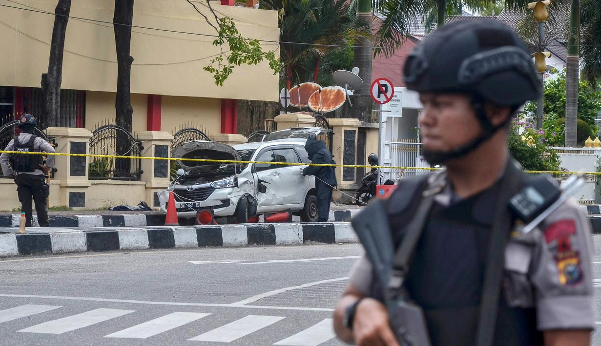 Polisi bersenjata berjaga di sekitar Mapolda Riau, Rabu (16/5). Sekelompok terduga teroris menyerang Mapolda Riau sambil membawa senjata tajam. (WAHYUDI/AFP)