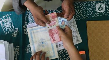 Warga menerima uang bantuan sosial tunai (BST) dari Kemensos di kawasan Kelurahan Kembangan, Meruya, Jakarta Barat, Minggu (25/07/2021). Kementerian Sosial (Kemensos) melalui PT Pos Indonesia mulai menyalurkan BST yang dirapel dua bulan sekaligus dengan total Rp600ribu (Liputan6.com/Herman Zakharia)