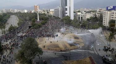 Polisi dan demonstran bentrok dalam protes anti-pemerintah di Santiago, Chile (4/10/2019). Ribuan warga Chile kembali turun ke jalan memprotes layanan sosial yang lebih baik. (AP Photo/Esteban Felix)