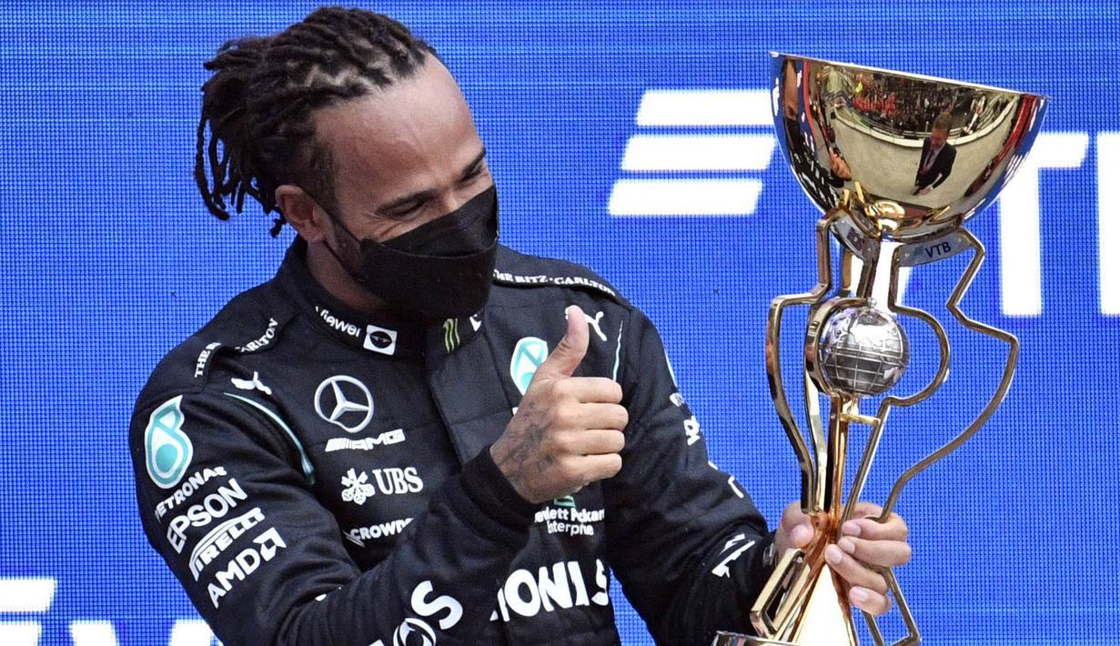 Pembalap Mercedes, Lewis Hamilton, mengunci kemenangan pada balapan F1 GP Rusia di Sirkuit Sochi, Minggu (26/9/2021). Kemenangan itu mengantar Hamilton mengukir sejarah baru. (AFP/Alexander Nemenov)