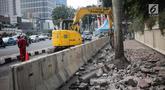 Pekerja dibantu alat berat merevitalisasi trotoar di kawasan Bundaran HI, Jakarta Pusat, Senin (15/7/2019). Penantaan ini dilakukan untuk mempercantik trotoar dan memberikan rasa nyaman bagi pejalan kaki. (Liputan6.com/Faizal Fanani)