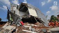 Petugas membersihkan puing longsor di kawasan Perumahan Pesona Kali Sari, Pasar Rebo Jakarta, Selasa (27/11). Dalam pembersihan tersebut, para petugas dibantu oleh satu unit alat berat yakni ekskavator. (Liputan6.com/Herman Zakharia)