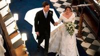 Putri Eugenie dari York dan Jack Brooksbank berjalan kembali menyusuri lorong setelah upacara pernikahan mereka di St George's Chapel, Windsor Castle, di Windsor, pada tanggal 12 Oktober 2018. (OWEN HUMPHREYS/AFP)