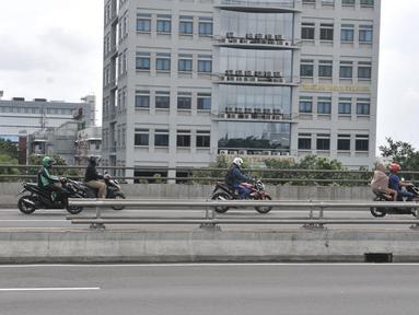 Pengendara motor melewati jalan tol di kawasan Cempaka Putih, Jakarta, Minggu (23/2/2020). Banjir yang melanda kawasan tersebut sejak dini hari tadi melumpuhkan akses di Jalan Ahmad Yani sehingga Gerbang Tol Pulomas dibuka untuk pengendara sepeda motor. (merdeka.com/Iqbal S. Nugroho)