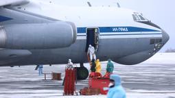 Petugas medis menyambut kedatangan warga yang turun dari pesawat militer di sebuah bandara luar Tyumen, Rusia, Rabu (5/2/2020). Rusia mengevakuasi 144 orang dari Wuhan yang terdiri dari warga Rusia, Belarus, Ukraina, dan Armenia menyusul wabah virus corona. (AP Photo/Maxim Slutsky)