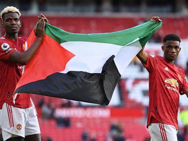 Paul Pogba dan Amad Diallo pun menjadi pesepakbola profesional yang mengekspresikan solidaritas mereka untuk rakyat Palestina. Keduanya memang merupakan pemain Muslim di skuad United. (Foto: AFP/Pool/Laurence Griffiths)