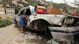 Seorang anak membeli permen di sebuah toko darurat di kawasan Jabal Sabr, Yaman pada 28 September 2019. Majd al-Din al-Shamiri (16) mengubah mobil keluarganya yang rusak parah, akibat perang yang melanda, menjadi toko darurat untuk mencari nafkah di tengah keadaan sulit. (Ahmad AL-BASHA/AFP)