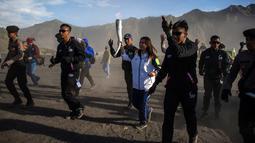 Legenda bulu tangkis Indonesia, Susi Susanti (tengah) membawa obor Asian Games 2018 di Gunung Bromo, Probolinggo, Jawa Timur, Sabtu (21/7). Sekitar 11 ribu atlet dari 45 negara Asia akan mengikuti Asian Games 2018. (JUNI KRISWANTO/AFP)