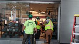 Pekerja membersihkan toko yang dijarah di pusat kota Chicago, AS (10/8/2020). Dua orang ditembak, lebih dari 100 lainnya ditangkap, dan 13 petugas polisi terluka dalam aksi penjarahan dan perusakan luas yang terjadi pada Senin (10/8) pagi waktu setempat di pusat kota Chicago. (Xinhua/Alan Ruffin)