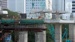 Para pekerja sedang menyelesaikan bentangan beton panjang light rail transit (LRT) di tikungan Jembatan 66 Kuningan-Dukuh Atas, Jakarta, Senin (6/7/2020). (merdeka.com/Dwi Narwoko)