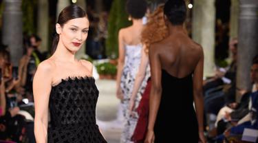 Model Bella Hadid berpose di atas catwalk mengenakan koleksi terbaru dari Oscar de la Renta dalam New York Fashion Week, AS (12/2). Bella Hadid tampil cantik dengan gaun hitam panjang tanpa lengan. (AFP Photo/Slaven Vlasic)