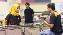 Petenis meja difabel Indonesia, Leli Marlina (kiri) menyimak arahan pelatih saat melawan Bee Tin Toh (Singapura) pada Indonesia Para Games Invitational Tournament 2018 di GBK Arena, Jakarta, Minggu (1/7). (Liputan6.com/Helmi Fithriansyah)