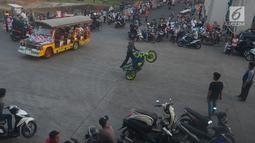 Sebuah mobil odong-odong melintas di tengah atraksi para freestyle di kawasan Kanal Banjir Timur, Jakarta, Selasa (29/5). Aksi berbahaya para rider di atas sepeda motor ini dilakukan pada saat ngabuburit menunggu bedug berbuka. (Merdeka.com/Imam Buhori)