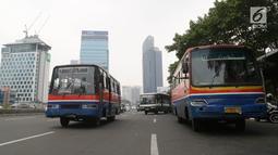 Bus Kopaja dan Metromini melintas di Jalan Jenderal Sudirman, Jakarta, Rabu (4/7). Larangan bagi Kopaja dan Metromini melintasi jalan protokol selama Asian Games untuk mengurangi kemacetan dan polusi di jalan protokol. (Liputan6.com/Arya Manggala)
