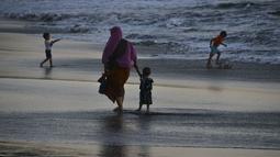 Seorang wanita bersama putranya berjalan di tepi pantai saat matahari terbenam di Banda Aceh pada 28 Juni 2019. Suasana eksotis menuju temaram bisa dinikmati sembari berjalan menyusuri pantai di tengah cahaya matahari yang mulai memerah. (Photo by CHAIDEER MAHYUDDIN / AFP)