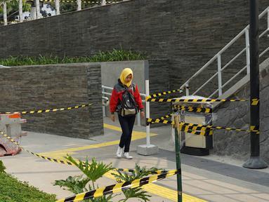 Pejalan kaki melewati proyek pembangunan Taman Dukuh Atas di Jalan Jenderal Sudirman, Jakarta, Jumat (2/8/2019). Pembangunan ruang terbuka baru di Dukuh Atas sebagai bagian dari penataan koridor Sudirman-Thamrin yang dilengkapi sarana olahraga dan anjungan pandang. (Liputan6.com/Immanuel Antonius)