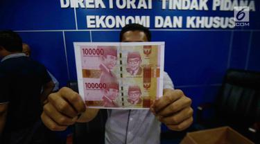 Uang palsu diperlihatkan saat rilis oleh Direktorat Tindak Pidana Ekonomi Khusus Bareskrim Polri, Jakarta, Kamis (7/11). Polisi mendapati barang bukti uang palsu pecahan Rp 100 ribu sebanyak 500 lembar siap edar. (Liputan6.com/Faizal Fanani)