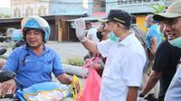 Foto : Wali Kota Kupang, Jefri Riwu Kore turun ke jalan membagikan masker gratis untuk pelintas jalan (Liputan6.com/Ola Keda)