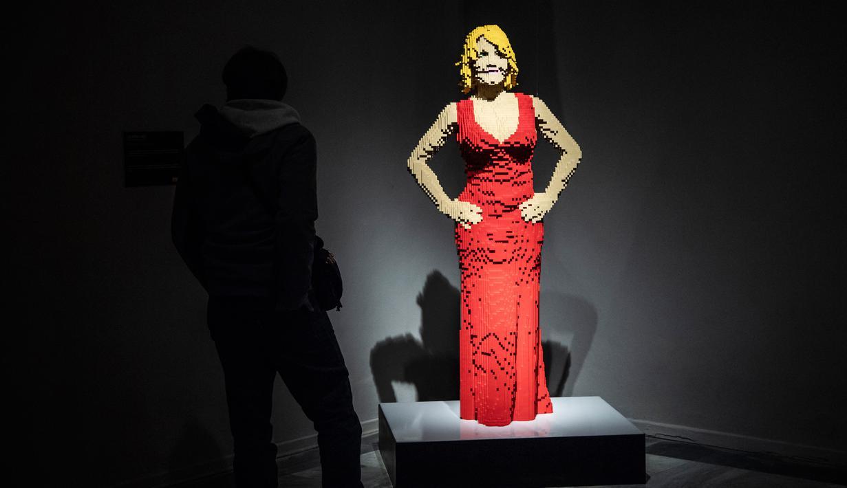 """Seseorang berdiri di dekat patung """"Courtney Red"""" yang terbuat dari susunan balok lego pada pameran Art of the Brick di Turin, Italia, Kamis (15/11). Pameran tersebut menampilkan berbagai patung lego karya seniman AS, Nathan Sawaya. (MARCO BERTORELLO/AFP)"""