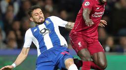 Winger Liverpool, Sadio Mane berebut bola dnegan bek FC Porto, Alex Telles pada leg kedua perempat final Liga Champions 2018/2019 di Estadio do Dragao, Rabu (17/4). Liverpool memastikan lolos ke babak semifinal Liga Champions setelah membantai FC Porto 4-1. (AP Photo/Luis Vieira)