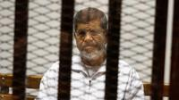 Mantan Presiden Mesir Mohammed Morsi duduk dalam penjara terdakwa di saat menjalani sidang di Akademi Kepolisian Nasional, Kairo, Mesir, 8 Mei 2019. Mohammed Morsi meninggal dalam sidang pengadilan pada Senin 17 Juni 2019 waktu setempat. (AP Photo/Tarek el-Gabbas, File)
