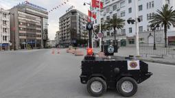 Robot polisi Tunisia berpatroli selama kebijakan penguncian (lockdown) di sepanjang Avenue Habib Bourguiba, pusat ibu kota Tunis, Rabu (1/4/2020). Selain untuk pengawasan dan pemberian sanksi, robot ini juga digunakan memberikan pesan agar warga Tunisia tetap berada di rumah. (FETHI BELAID/AFP)