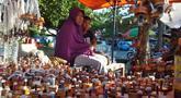 Pedagang menunggu pembeli saat berjualan pelita di Jalan Sam Ratulangi, Kota Gorontalo, Rabu (22/5/2019). Sejumlah pedagang menjual pelita dari botol bekas untuk menyambut perayaan Tumbilotohe atau malam pasang lampu yang digelar tiga hari menjelang Idul Fitri di Gorontalo. (Liputan6.com/Arfandi Ibr