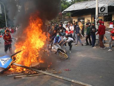 Pelajar membakar sepeda motor dan rambu lalu lintas saat berdemonstrasi di belakang Gedung DPR, Palmerah, Jakarta, Rabu (25/9/2019). Selain membakar sejumlah benda, para pelajar juga melempari Gedung DPR dengan batu. (Liputan6.com/Angga Yuniar)