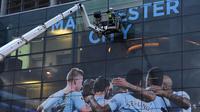 Pekerja memasang poster raksasa bergambar pemain Manchester City terpasang di Stadion Etihad, Manchester, Senin (17/4/2018). Persiapan ini dilakukan untuk merayakan pesta juara Manchester City meraih gelar Premier League. (AFP/Paul Ellis)