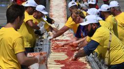 Sejumlah peserta mengoleskan saus tomat saat membuat pizza panjang di jalur Auto Club Speedway, di Fontana, California (10/6). (AFP/Mark Ralston)