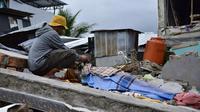 Seorang pria berduka atas jenazah korban gempa di Kota Mamuju, Sulawesi Barat, Indonesia, Jumat (15/1/2021). BMKG menyebut pusat gempa berada di darat, 6 kilometer timur laut Majene pada kedalaman 10 kilometer. (Firdaus/AFP)