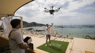 Pilot mengikat sekantong makanan ke drone dari Cala Tadira dekat Sant Josep de Sa Talaia di Pulau Ibiza, Spanyol, 24 Agustus 2021. Restoran Can Yucas dan perusahaan Galicia Aerocamaras meluncurkan layanan Drone to Yacht untuk mengirim makanan dan minuman eksklusif ke kapal pesiar. (JAIME REINA/AFP)