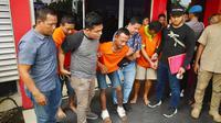 Eksekutor pembunuhan pengusaha tepung di Pekanbaru meringis kesakitan karena dua kakinya ditembak personel Polda Riau. (Liputan6.com/M Syukur)