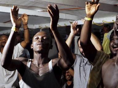 Para imigran di atas kapal Open Arms merayakan berita tentang seorang jaksa penuntut Italia yang telah memerintahkan bahwa para migran akan turun di pulau Lampedusa, Italia selatan (20/8/2019). Setidaknya 15 migran lainnya melompat ke laut dari kapal Open Arms untuk menuju pantai Italia. (AP Photo/F