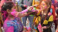 Anak-anak umat Hindu bermain dengan bubuk berwarna ketika merayakan festival keagamaan Holi di Kuil Swupramayan Kalupur, Ahmedabad, Rabu (20/3). Walaupun Holi merupakan festival Hindu, namun seluruh penduduk India merayakannya. (SAM PANTHAKY / AFP)