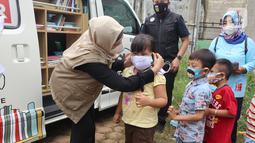 Karyawan Askrindo memberikan masker kain kepada anak-anak korban banjir di Kantor Kecamatan Cilamaya Wetan, Cikampek Jumat (12/02/2021). Askrindo melakukan aksi tanggap bencana banjir di dua lokasi di Karawang dengan memberikan bantuan sembako dan makanan siap saji. (Liputan6.com/Pool/Askrindo)