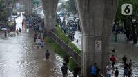 Warga menyusuri Jalan Kapten Tendean yang terendam banjir, Jakarta, Sabtu (20/2/2021). Banjir yang disebabkan curah hujan tinggi memutus akses lalu lintas di Jalan Kapten Tendean. (merdeka.com/Imam Buhori)
